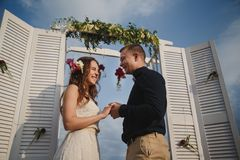 Outdoor beach wedding ceremony, stylish happy smiling groom and bride are standing near wedding altar on the sea shore holding han Stock Images