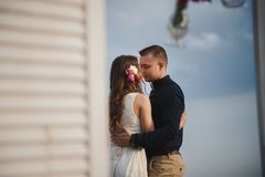 Outdoor beach wedding ceremony, stylish happy smiling groom and bride are standing near wedding altar on the sea shore, hugging Royalty Free Stock Photos