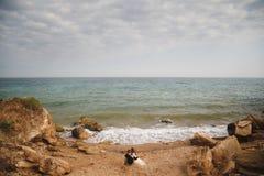 Outdoor beach wedding ceremony, stylish wedding loving couple is sitting near the sea Royalty Free Stock Images
