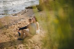 Outdoor beach wedding ceremony, stylish wedding loving couple is sitting near the sea stock images