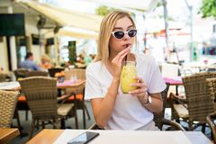 Outdoor fashion beauty portrait of elegant lady with eyes sunglasses, drinking tasty cold cocktails, city cafe terrace, travel, jo stock photo