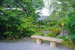 Outdoor bench, green plants, road and pavilion in Japanese zen g. The outdoor bench, green plants, road and pavilion in the Japanese zen garden royalty free stock images