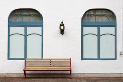 Outdoor bench with white wall. On brick street Stock Photos