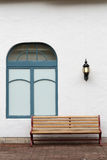 Outdoor bench with white wall. On brick street Royalty Free Stock Photography