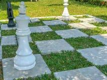 Outdoor big chess and Checkered flag. In the garden Stock Photos