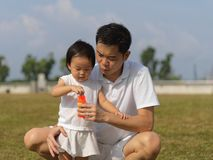 Outdoor bonding between father and daughter with bubble play. Outdoor bonding between father and daughter blowing bubbles in a park Royalty Free Stock Photo