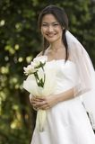 Outdoor Bride 2. A beautiful young asian woman in a wedding dress poses outside Stock Photography