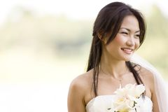 Outdoor Bride 3. A beautiful asian bride poses outside stock photos