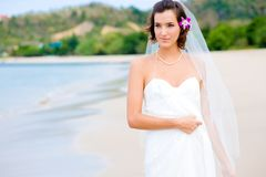 Outdoor Bride. A young bride in wedding dress on a tropical beach Royalty Free Stock Photo