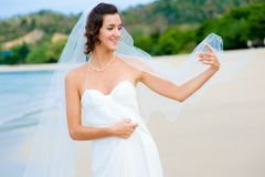Outdoor Bride. A young bride in wedding dress on a tropical beach Stock Photos