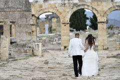 Outdoor Bride and Groom. Outdoor bride walking in the pamukkale, hierapolis morning golden sunlight Royalty Free Stock Image