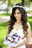 Outdoor Bride smiling. Outdoor bride looking at flower in natural park Stock Photos