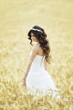 Outdoor Bride smiling. Outdoor bride walking in wheat field by natural morning golden sunlight Stock Photo