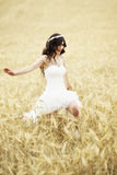 Outdoor Bride smiling. Outdoor bride walking in wheat field by natural morning golden sunlight Royalty Free Stock Photos