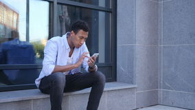 Outdoor Browsing on Smartphone, Young Black Handsome Man. Outdoor Browsing on Smartphone, Sitting Young Black Handsome Man, Creative designer , businessman stock video footage