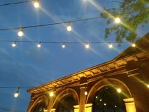 Outdoor Building with lights pop up beer garden. City sights at dusk royalty free stock photos