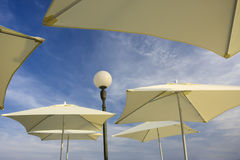Outdoor cafe. White umbrellas against blue sky Royalty Free Stock Images