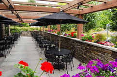 Outdoor Cafe. Rows of empty black chairs and tables with black umbrellas in outdoor open air patio enclosed by brick half wall with vivid, colorful flowers Royalty Free Stock Photography