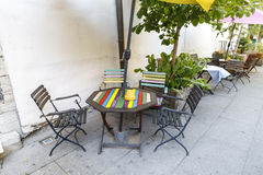 Outdoor cafe with a colorful table. Colorful outdoor cafe tables and chairs near yellow wall Royalty Free Stock Image