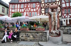 Outdoor cafe, Knight of Hattstein statue, town centre of Limburg, Germany. The outdoor cafe and Knight of Hattstein statue the `drunkard` fountain in the old Stock Photo