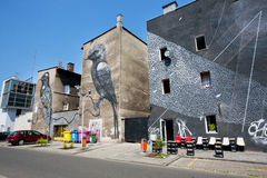 Outdoor cafe in the modern buildings with funny street art pictures Stock Photo