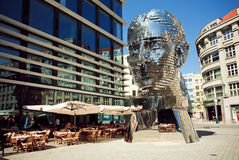 Outdoor cafe near  famous artist David Cerny's sculpture Metalmorphosis in giant head form Stock Photos
