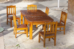 Outdoor cafe patio with old, shabby wooden tables and chairs in the sunlight photo Stock Photography
