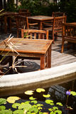 Outdoor cafe patio with old, shabby wooden tables and chairs Stock Photos