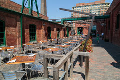 Outdoor cafe prepared to serve customers at old vintage Toronto distillery historic district. Toronto city, Ontario, Canada, May 22, 2016, Outdoor cafe prepared Royalty Free Stock Images