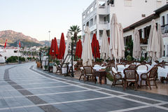 Outdoor cafe and restaurant of Marmaris with mountains on background. MARMARIS, TURKEY - SEPTEMBER 11: Outdoor cafe and restaurant on sea-front street of Stock Image