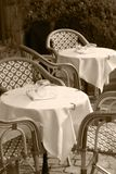 Outdoor cafe and restaurant with tables, chairs and glasses waiting for customers to arrive in black and white sepia tone. Stock image royalty free stock image