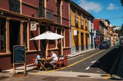 Outdoor cafe on street in La Laguna. La Laguna, Tenerife, Canary islands, Spain - May 23, 2017. People relax and enjoy their drinks and food at outdoor cafe Royalty Free Stock Image