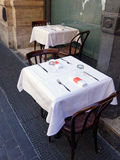 Outdoor Cafe Tables, Rome, Italy. Two outdoor cafe tables neatly set with white tablecloths, knives and forks, waiting for the day`s first customers, Rome, Italy Royalty Free Stock Photography