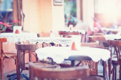 An outdoor cafe with vintage chairs, white table cloths. Royalty Free Stock Photos