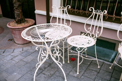 Outdoor cafe with white wrought-iron furniture, Vilnius. Openwork white table and two white fishnet chair of iron, standing in the street Stock Image