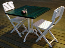 Outdoor caffe. Two white chairs wth a green table Royalty Free Stock Images