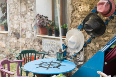 Outdoor caffee table decorated with lantern and summer hats. Table of blue color with black steering wheel painted on tabletop chairs of green and purple color Stock Images