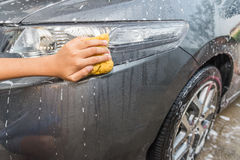 Outdoor car wash with yellow sponge. Royalty Free Stock Image