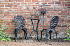 Outdoor. Cast iron garden furniture suit next to brick wall Stock Photography