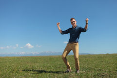 Outdoor casual man cheers on a green plain Stock Image