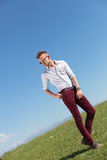 Outdoor casual man holds his belt and looks away Royalty Free Stock Images