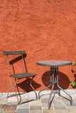 Outdoor chair and table. Empty chair and table on a terrace before an orange wall Royalty Free Stock Images