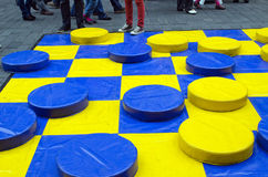 Outdoor checkers game figures yellow blue people. Yellow and blue huge checkers figures outdoor and many people legs. people fun entertainment play object in royalty free stock images