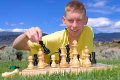 Outdoor chess. Teen plays chess outdoor on sunny day Royalty Free Stock Image
