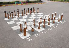 Outdoor chess. Wooden chess big pieces on asphalt Royalty Free Stock Image