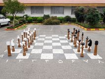 Outdoor chess. Wooden chess big pieces on asphalt Royalty Free Stock Photography