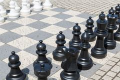 Outdoor chess board with plastic pieces Royalty Free Stock Image