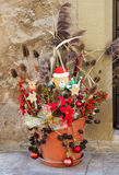 Outdoor christmas decoration with a teddy santa and dry plants. Stock Image