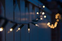 Outdoor christmas lights at night. Christmas lights in subdued light draped over residential fence Royalty Free Stock Images