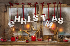 Outdoor christmas window decoration with red candles, deer and t Royalty Free Stock Photo